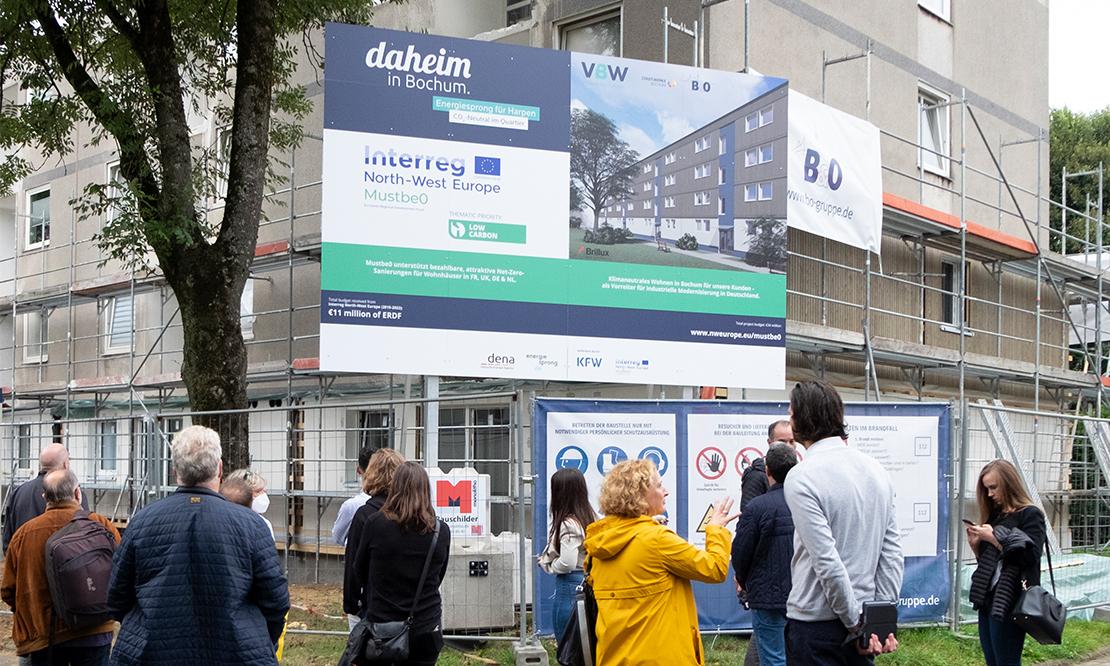 Interessierte stehen vor dem Bauschild des Energiesprong-Piloten an der Mörikestraße 8 - 14 in Bochum